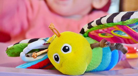 Kleine Grafik zum Thema Baby und Kind mit einem bunten Schmetterling als Greifling