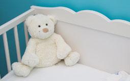 Kleine Grafik zum Thema Babybett mit einem weißen Bett vor blauer Wand