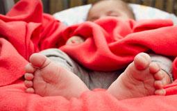 Kleine Grafik zum Thema Babydecke mit einem Baby in einer roten Decke liegend