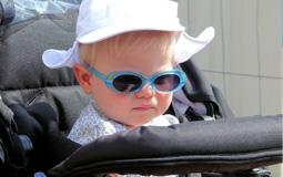 Kleine Grafik zum Thema Kinderwagen - Kleinkind sitzt mit blauer Sonnenbrille und Hut im Kinderwagen