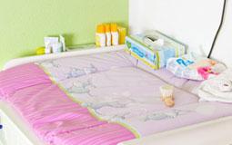 Kleine Grafik zum Thema Wickeltisch mit einer weißen Wickelkommode mit rosanem Bezug