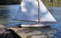 Kleine Grafik zum Thema Modellbau mit einem Modellsegelschiff im Wasser