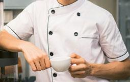 Kleine Grafik zum Thema Arbeitskleidung mit einem Koch in weißer Kochjacke, der eine Tasse in der Hand hält