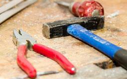 Kleine Grafik zum Thema Werkbank mit einem Hammer, Schraubendreher und einer Kombizange auf einer Werkbank