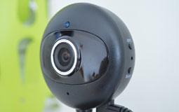 Kleine Grafik zum Thema Webcams mit einer schwarzen Webcam vor grün-weißem Hintergrund
