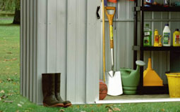 Kleine Grafik zum Thema Garten mit einem grauen, offenen Geräteschuppen mit gelagertem Gartenzubehör