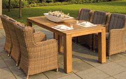 Kleine Grafik zum Thema Gartengarnitur mit einer hellen Polyrattan-Sitzgruppe an einem Holztisch