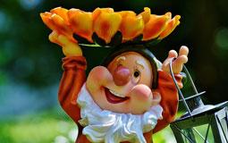 Kleine Grafik zum Thema Gartenfigur mit einem Gartenzwerg, der eine Blüte und eine Laterne hochhält