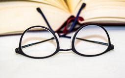 Kleine Grafik zum Thema Brillen mit einer schwarzen Lesebrille vor einem Buch liegend