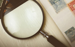 Kleine Grafik zum Thema Lupen mit einer Lupe auf einem Briefmarkenalbum liegend
