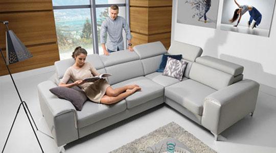 Grafik zum Thema Sofas - Frau liest Magazin auf grauer Couch