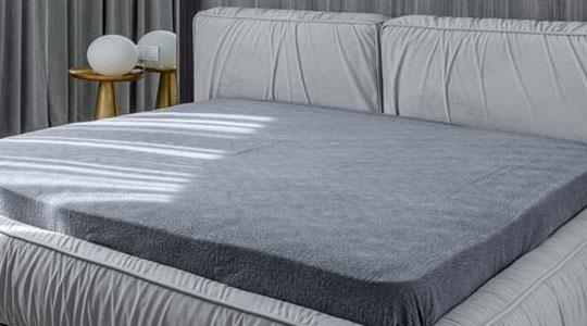Grafik zum Thema Matratzen mit einer grauen Matratze auf einem hellgrauen Bett