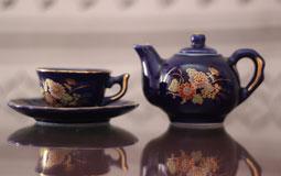 Kleine Grafik zum Thema Antiquitäten mit blauer Porzellankanne und blauer Porzellantasse auf einem spiegelnden Tisch