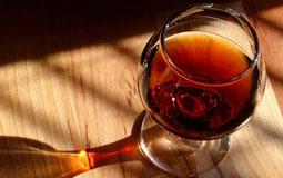 Kleine Grafik zum Thema Cognac mit einem gefüllten Cognacglas auf einem Holztisch