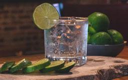 Kleine Grafik zum Thema Gin mit einem Ginglas auf einem Holzbrett und mehreren Limettenscheiben