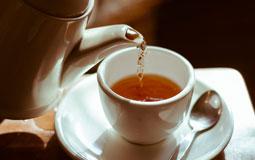 Kleine Grafik zum Thema Tee mit einer Teekanne, die Tee in eine weiße Tasse gießt