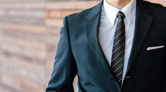 Grafik zum Thema Herrenmode - Mann mit Hemd, gestreifter Krawatte und dunklem Anzug lehnt sich an Holzwand