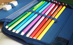 Kleine Grafik zum Thema Schule mit einem blauen Federmäppchen gefüllt mit Buntstiften
