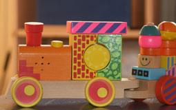 Kleine Grafik zum Thema Holzspielzeug mit einer bunten Holzeisenbahn