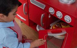 Kleine Grafik zum Thema Spielzeug mit einem kleinen Jungen vor einer roten Spielküche