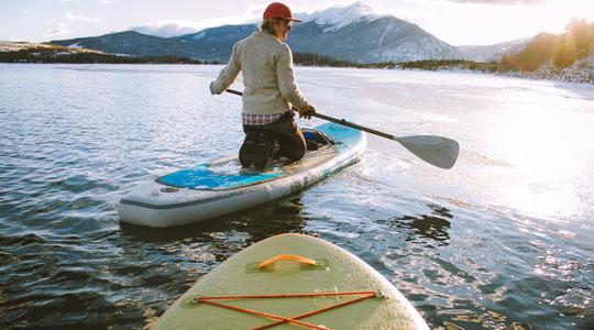 Grafik zum Thema Paddle Board mit einer Paddle Boarderin, die auf einem Bergsee paddelt