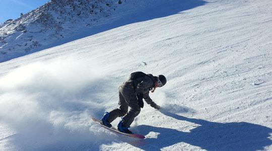 Grafik zum Thema Snowboards mit einem Snowboarder, der gerade einen Abhang runterfährt und sich in die Kurve neigt