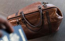 Kleine Grafik zum Thema Reisen mit einer braunen Reisetasche