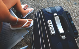 Kleine Grafik zum Thema Reisen mit einem Reisekoffer vor Frauenbeinen in Flip-Flops