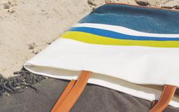 Kleine Grafik zum Thema Reisen mit einer Strandtasche, die im Sand liegt