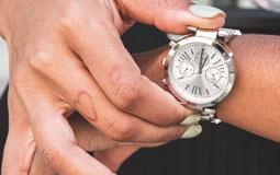 Kleine Grafik zum Thema Damenuhren mit einer Frauenhand, die nach einer weiß-silbernen Uhr greift