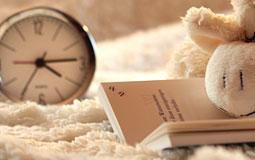 Kleine Grafik zum Thema Kinderuhren mit einer Uhr, die gemeinsam mit einem Buch und einem Kuscheltier auf einer Decke liegt