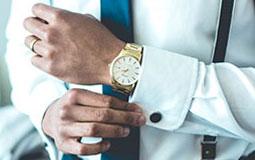 Kleine Grafik zum Thema Luxusuhren mit einem stilvoll gekleideten Mann, der sein Ärmel richtet und eine goldene Uhr trägt