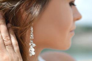 Kleine Grafik zum Thema Perlenschmuck mit einer Frau, die Ohrringe mit Perlen in der Hand hält