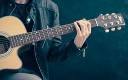 Kleine Grafik zum Thema Musikinstrumente mit einem Gitarrenspieler