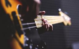 Kleine Grafik zum Thema Musikinstrumente mit einem E-Bass in den Händen eines Bassisten