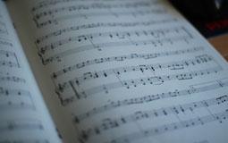 Kleine Grafik zum Thema Musik mit einem geöffnetem Notenheft