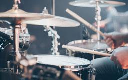 Kleine Grafik zum Thema Musikinstrumente mit einem Schlagzeug, das gerade gespielt wird