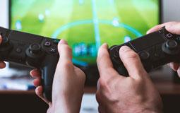 Kleine Grafik zum Thema Gaming mit zwei hochgehaltenen PS4-Controllern vor einem Fernseher