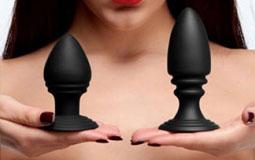 Kleine Grafik zum Thema Sex-Toys mit einer Frau, die zwei schwarze Anal-Plugs mit den Händen hochhält