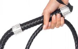 Kleine Grafik zum Thema Sexzubehör mit einer Damenhand, die eine schwarze Peitsche umgreift