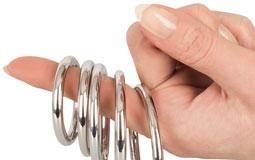 Kleine Grafik zum Thema Sexzubehör mit einer Damenhand, die fünf silberne Penisringe mit dem Zeigefinger hochhält