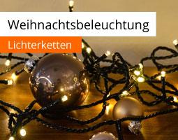 Kleine Grafik zum Thema Weihnachtsbeleuchtung mit einer Lichterkette, die gemeinsam mit Weihnachtskugeln auf einem Holztisch liegt