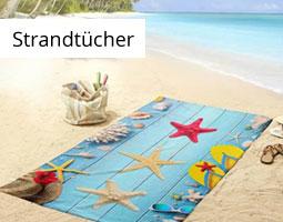 Kleine Grafik zum Thema Strandtücher mit einem bunten Strandtuch auf Sand ausgebreitet und mit Muschel-Motiv