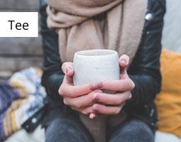 Kleine Grafik zum Thema Tee mit einer jungen Frau, die draußen auf Decken sitzt und eine Tasse in beiden Händen hält