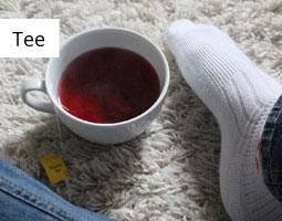 Kleine Grafik zum Thema Tee mit einer Tasse Tee, die unten auf einer Wolldecke liegt