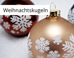 Kleine Grafik zum Thema Weihnachten mit einer roten und einer bronzenen Weihnachtskugel mit weißen Schneeflocken