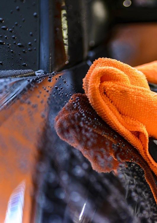 Vibes-Kachel zum Thema Autopflege mit einem nassen schwarzen Auto, welches mit einem orangenen Lappen geputzt wird