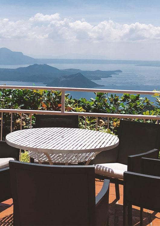 Vibes-Kachel zum Thema Balkonmöbel mit einer Tischgruppe auf einem Balkon vor einer traumhaften Aussicht