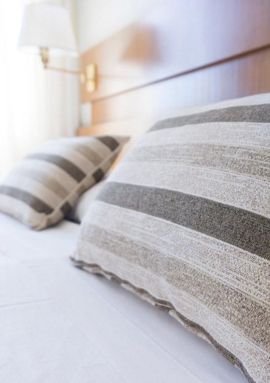 Bett mit zwei gestreiften Kissen