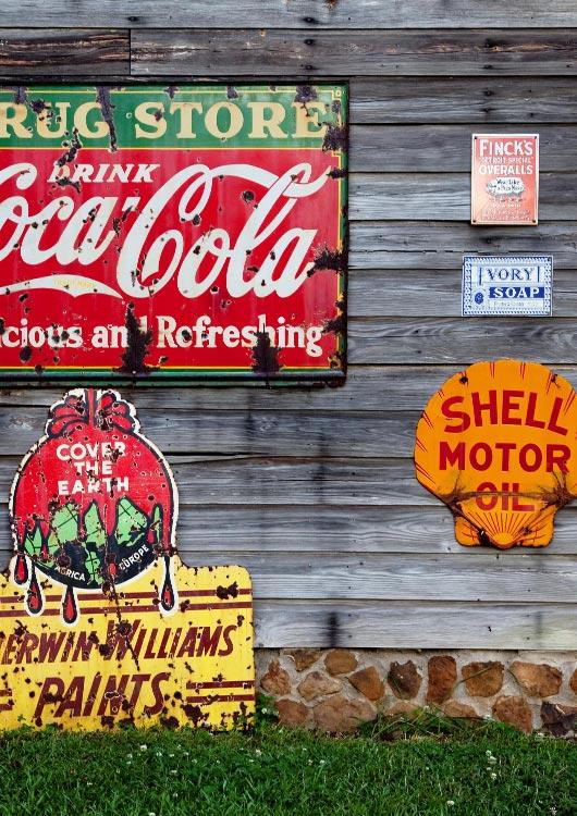 Vibes-Kachel zum Thema Sammeln & Seltenes mit unterschiedlichen Retro-Werbeschildern an einer Holzwand hängend